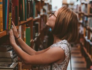 woman in library looking at bookshelf