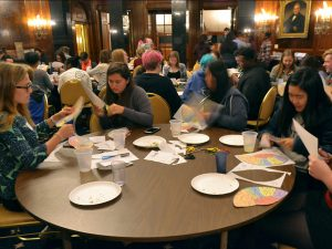 Teens around a table cut paper brains as part of a Teen Science Cafe