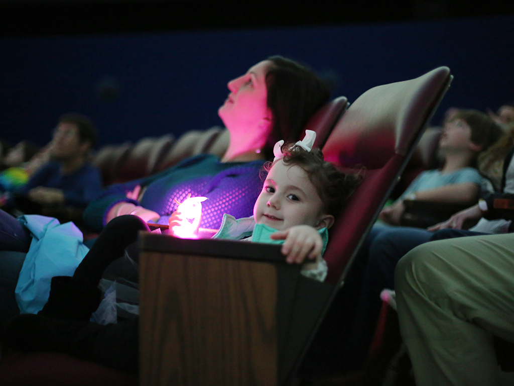 Child enjoying planetarium show in theater with parent