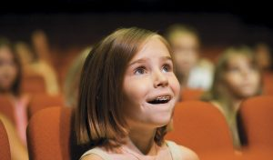 little girl in theater looking up in awe