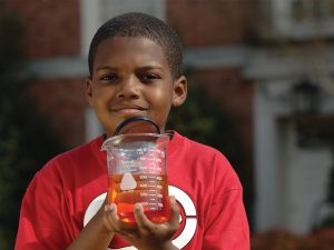 Boy holding beaker filled with orange liquid in one hand and a magnifying glass in the other
