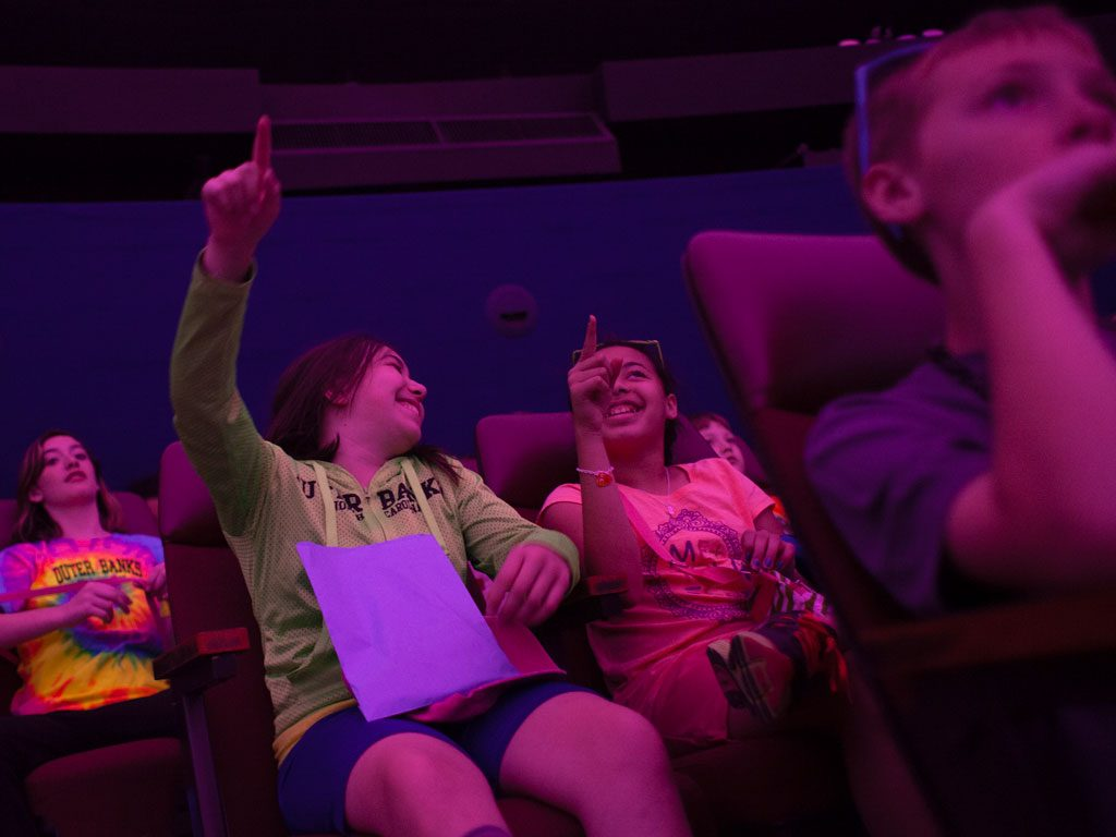 A group of students point up at the fulldome theater at Morehead Planetarium and Science Center