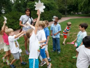 Kids play outside with paper fans and bubbles