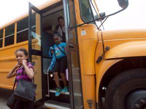 Kids getting off a school bus