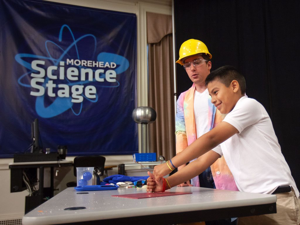 Student participating in science demonstration