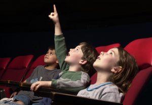 Three kids view planetarium show in fulldome theater