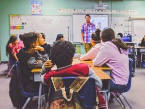 Children sitting in a classroom facing teacher