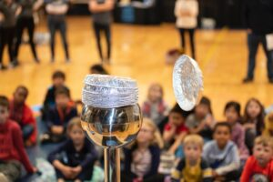 Children onlooking science demonstartion in gymnasium